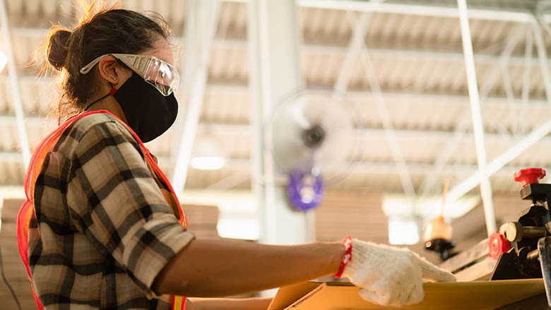 A female factory worker wears a mask while cutting wood